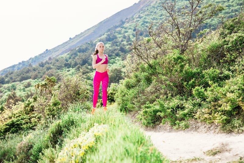 Jeune femme en bonne santé de forme physique courant sur la nature photographie stock