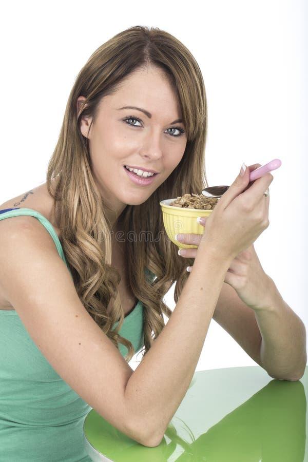 Jeune femme en bonne santé mangeant le bol de céréales de petit déjeuner image stock