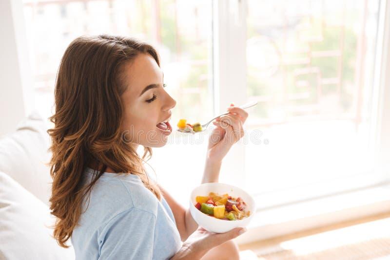 Jeune femme en bonne santé mangeant le petit déjeuner sain photo libre de droits