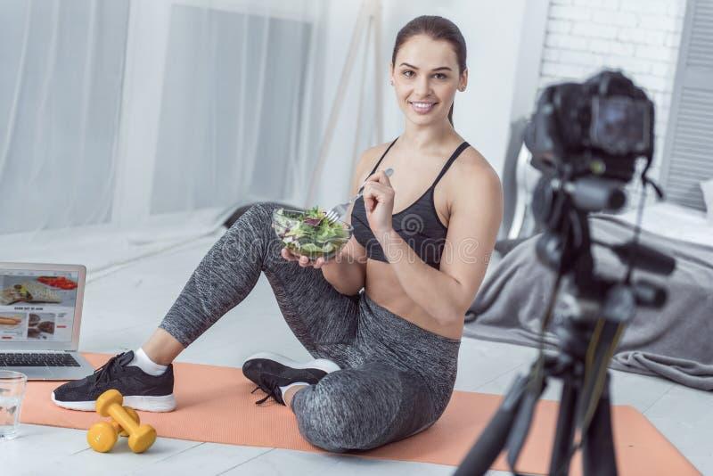 Jeune femme en bonne santé positive mangeant de la salade savoureuse photo stock