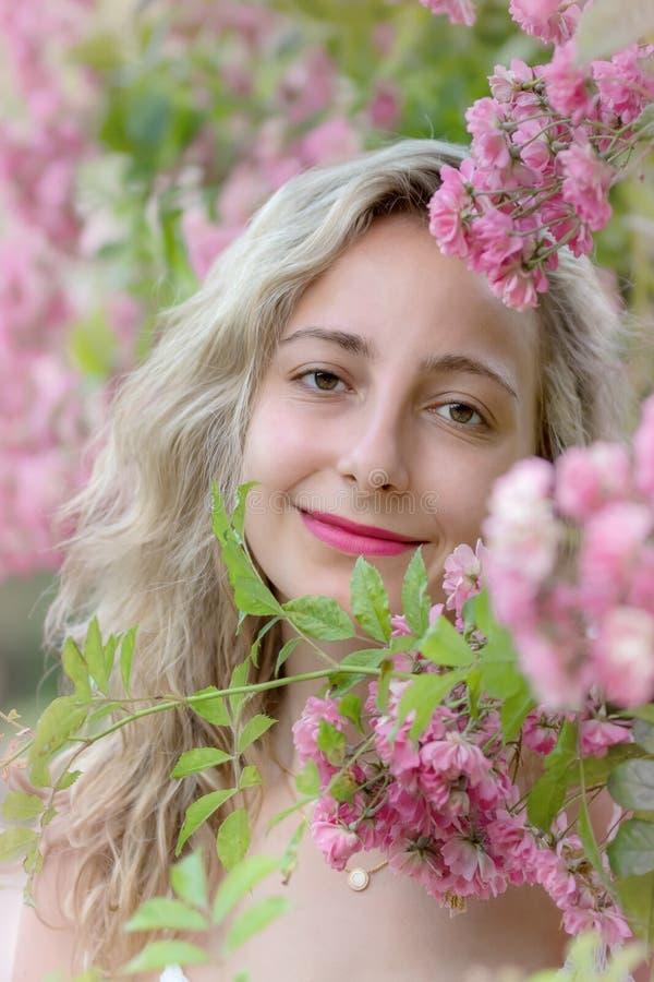 Jeune femme en parc des roses photo stock