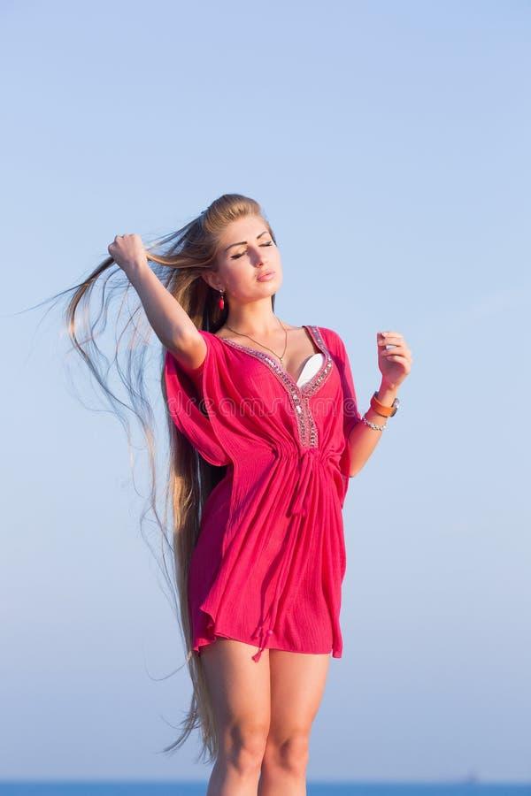 Jeune femme en rouge ajustant ses cheveux dehors photo libre de droits