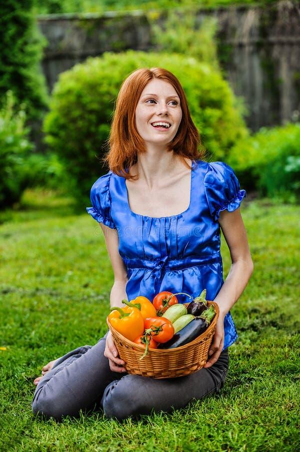 Jeune femme en se reposant sur la pelouse avec le panier végétal photos stock