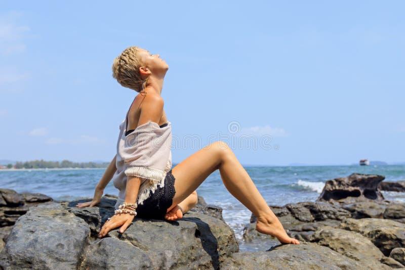 Jeune femme en toiles blanches et de fond se reposant sur le bord de la mer rocheux photographie stock libre de droits