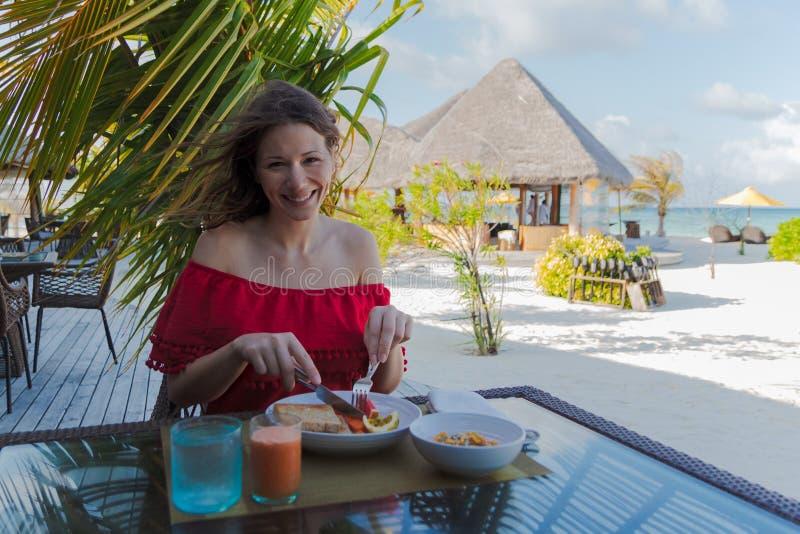 Jeune femme en vacances en île tropicale mangeant un petit déjeuner sain photo stock