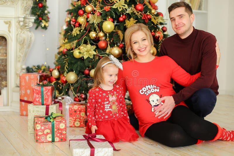 Jeune femme enceinte blonde s'asseyant avec le mari et la petite fille près des cadeaux sous l'arbre de Chistma photos stock