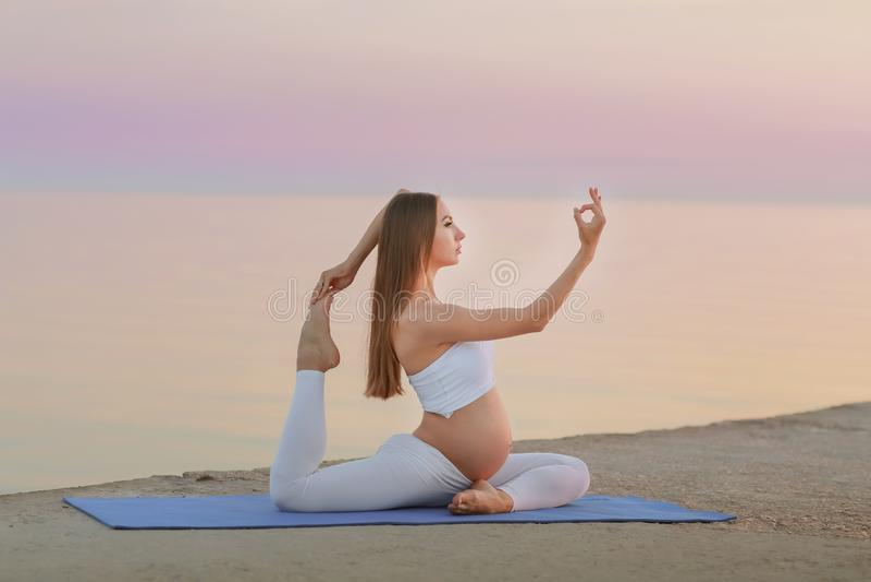 Jeune femme enceinte dans la robe blanche se reposant sur la plage près de la mer bleue et respirant Vacances d'été pendant la gr image stock