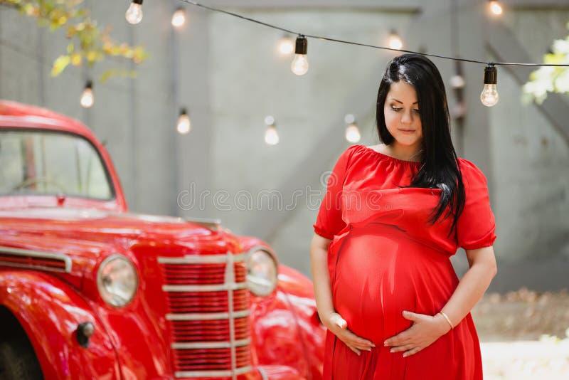 Jeune femme enceinte dans un jardin d'automne près de rétro voiture rouge photographie stock libre de droits