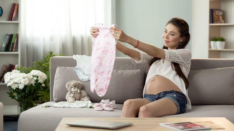 Jeune femme enceinte excitée regardant les vêtements nouveau-nés, achats de mode de bébé photographie stock libre de droits