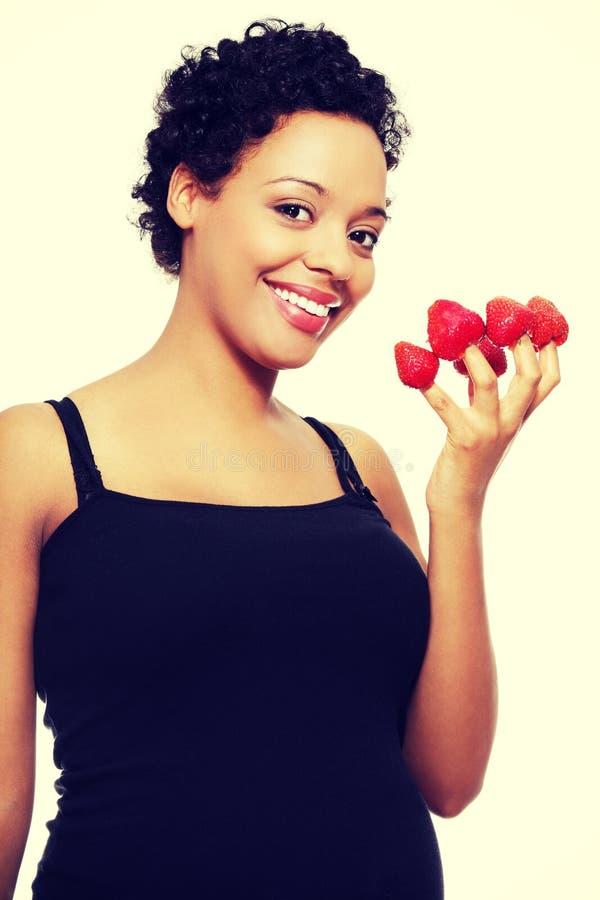 Jeune femme enceinte heureuse avec des fraises photo libre de droits