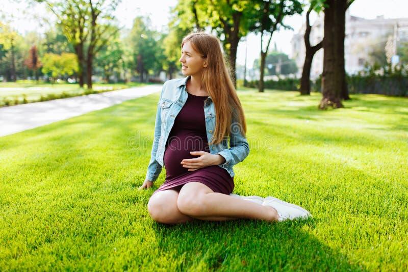 Jeune femme enceinte heureuse s'asseyant en parc sur la pelouse images stock