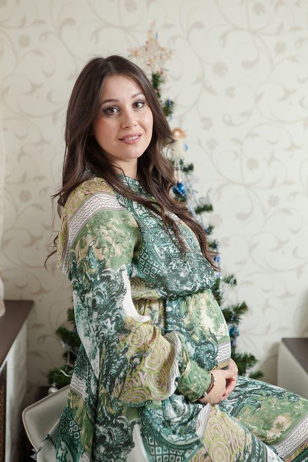 Jeune femme enceinte heureuse s'asseyant près de l'arbre de Noël photo stock