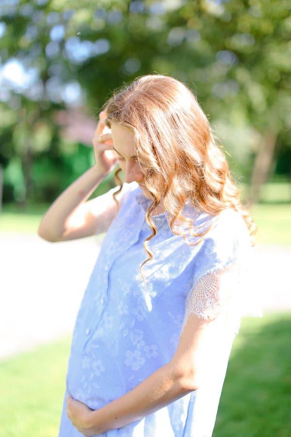 Jeune femme enceinte heureuse utilisant le ventre bleu de participation de robe image stock