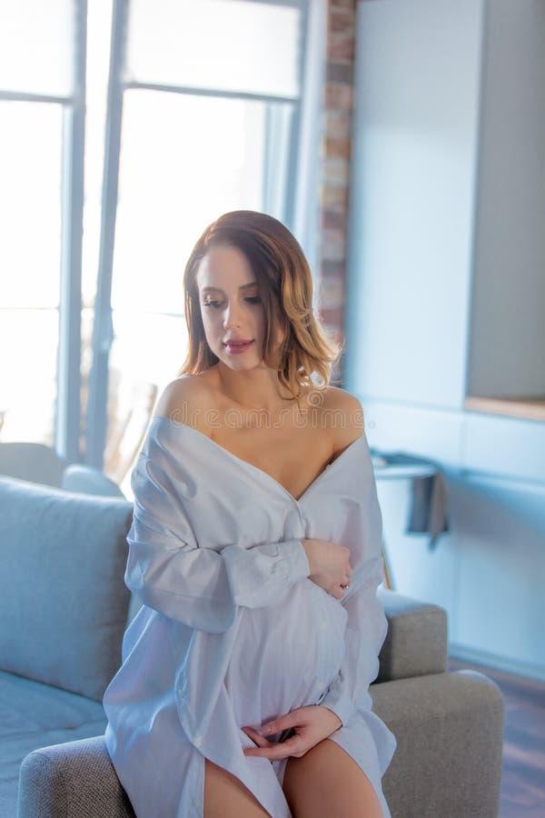 Jeune femme enceinte rousse dans des vêtements blancs photo libre de droits