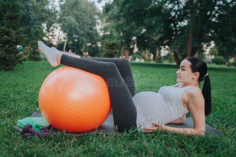 Jeune femme enceinte souffrir de la douleur dans le secteur de hanches Elle se trouvant sur le compagnon de yoga en parc Mains mo photo stock