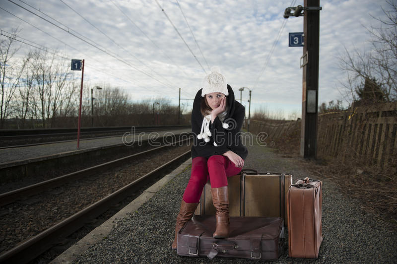 Jeune femme ennuyée dans des vêtements de l'hiver attendant son train photo stock
