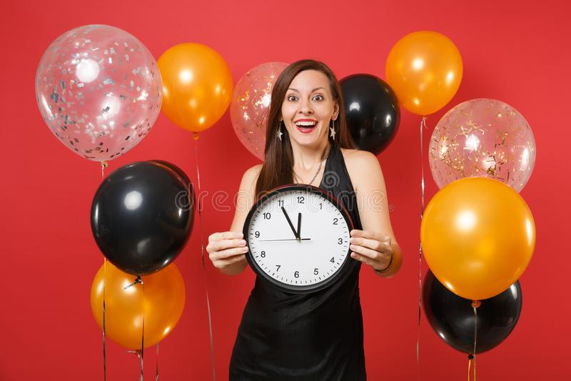 Jeune femme enthousiaste dans la robe noire célébrant tenant l'horloge ronde sur le ballon à air rouge lumineux de fond Le temps  images stock