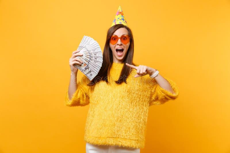 Jeune femme enthousiaste dans les verres de coeur et le chapeau oranges d'anniversaire dirigeant l'index sur un bon nombre de paq photos stock