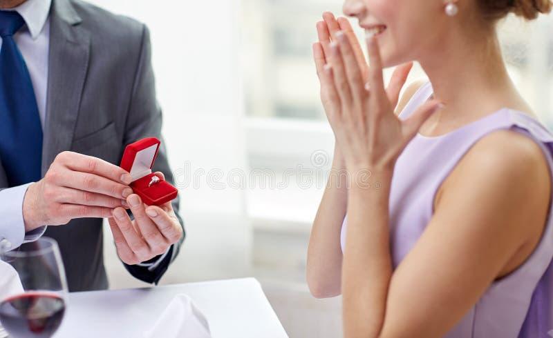 Jeune femme enthousiaste et ami donnant son anneau images libres de droits