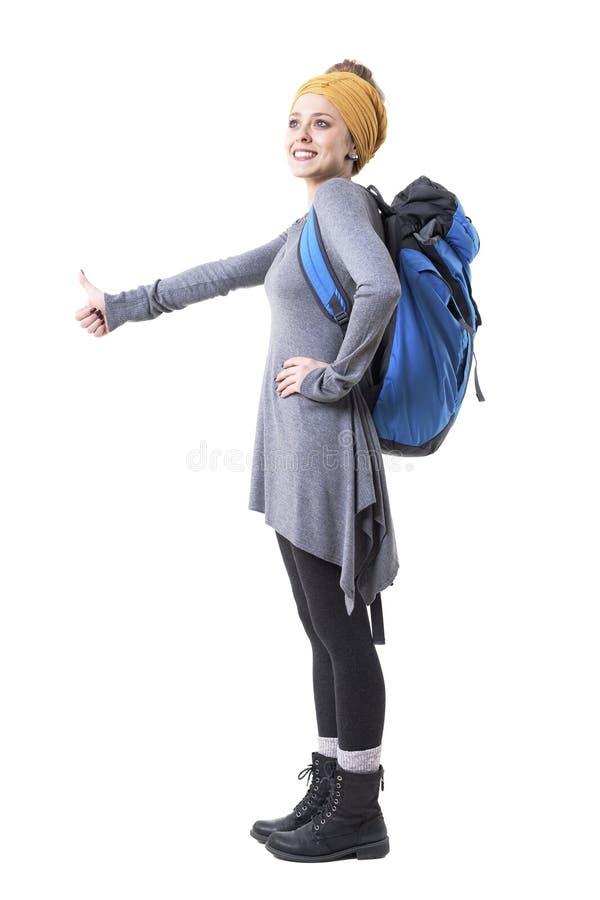 Jeune femme enthousiaste heureuse avec le sac à dos faisant de l'auto-stop avec le pouce vers le haut du sourire et du regard loi image libre de droits