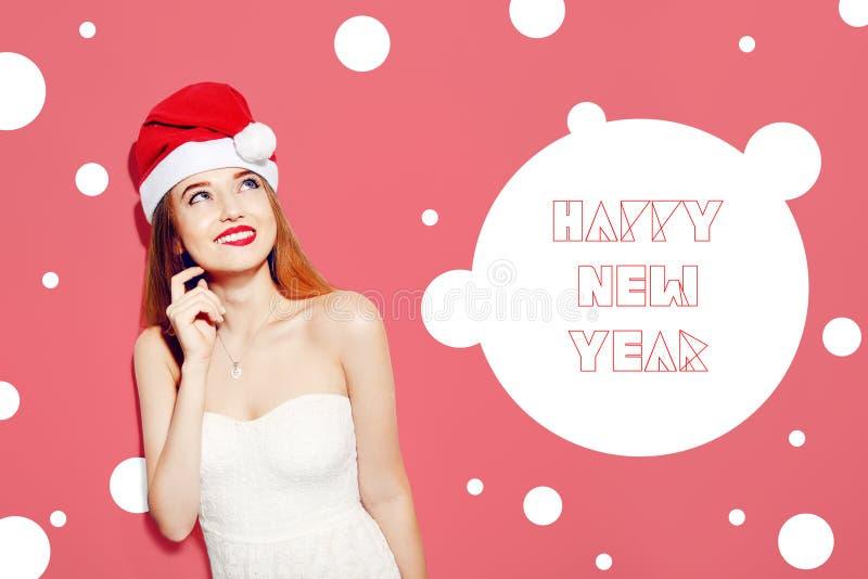 Jeune femme enthousiaste heureuse dans le chapeau du père noël pensant au-dessus du fond rose Fille mignonne dans la robe blanche images libres de droits