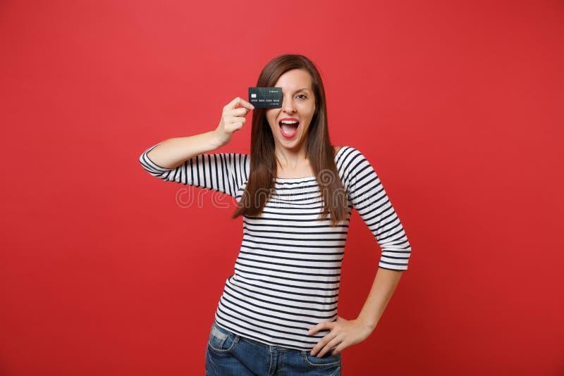 Jeune femme enthousiaste maintenant la bouche grande ouverte, regardant étonné, couvrant l'oeil de carte de crédit d'isolement su image stock
