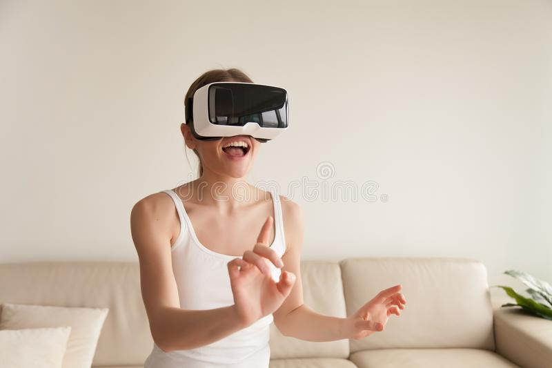Jeune femme enthousiaste portant la réalité virtuelle émouvante de casque de VR image libre de droits