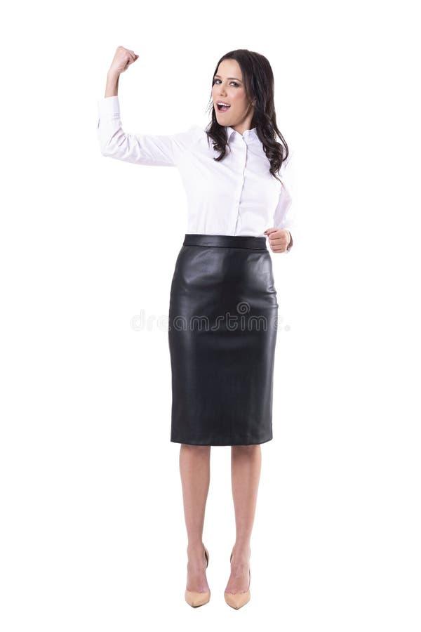 Jeune femme enthousiaste réussie d'affaires fléchissant le bras célébrant le but ou l'accomplissement de carrière photographie stock