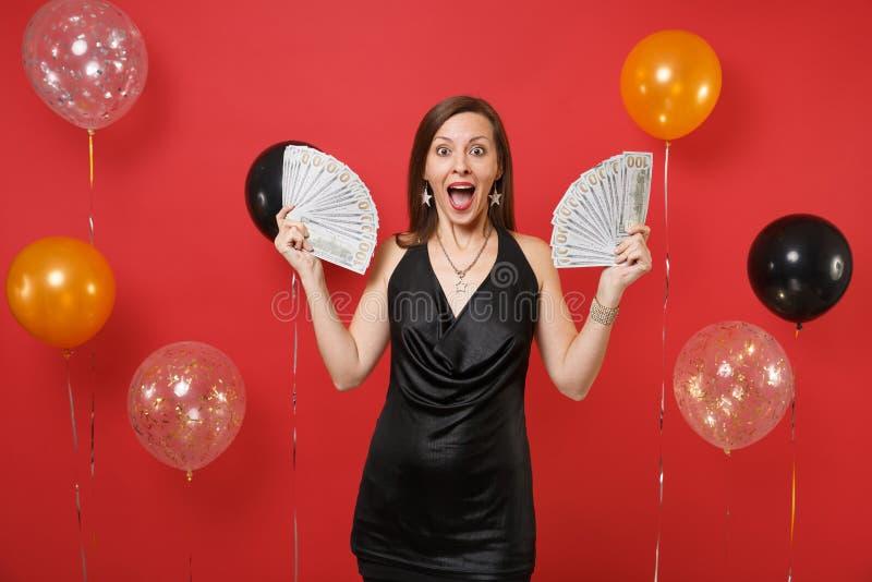Jeune femme enthousiaste Surprised dans peu de célébration noire de robe, tenant un bon nombre de paquet de dollars, argent d'arg images libres de droits