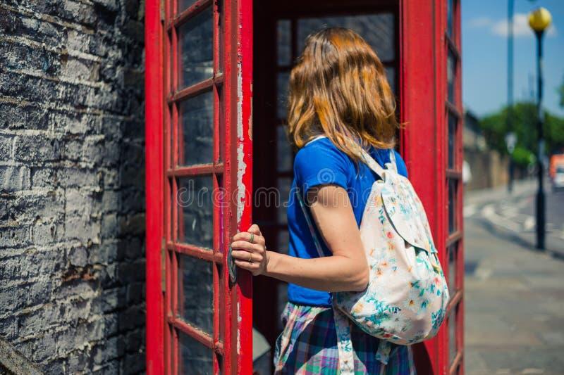 Jeune femme entrant dans une cabine de téléphone image stock