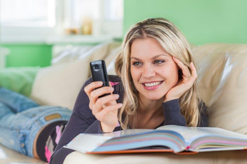 Jeune femme envoyant SMS avec le téléphone portable tout en se trouvant à la maison dessus image stock