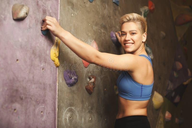 Jeune femme escaladant le mur artificiel de roche au gymnase photo libre de droits