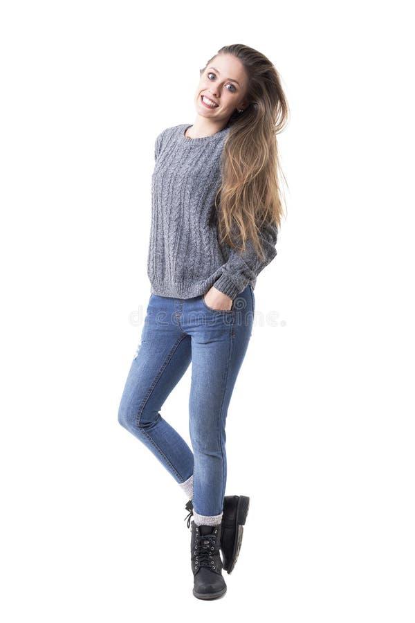 Jeune femme espiègle heureuse mignonne dans le pullover gris avec de longs cheveux blonds sains image stock