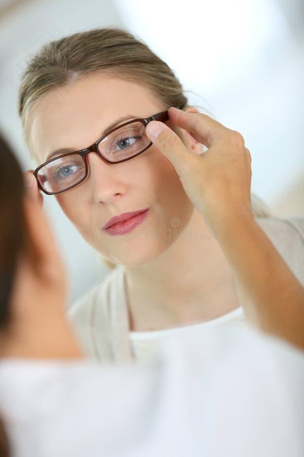 Jeune femme essayant sur de nouvelles lunettes photos stock