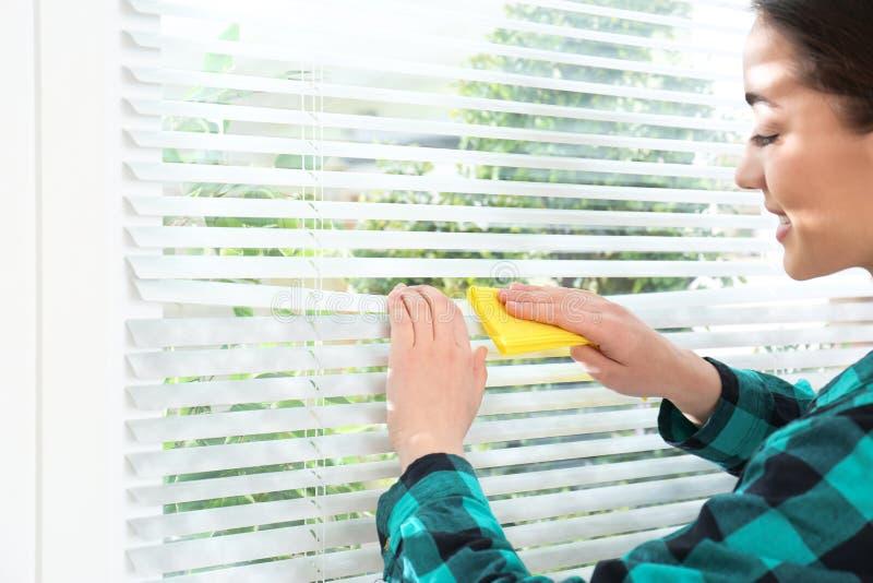 Jeune femme essuyant des abat-jour de fenêtre avec du chiffon Avant et apr?s le nettoyage photo libre de droits