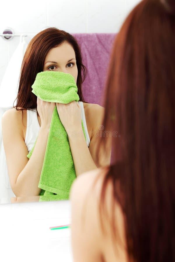 Jeune femme essuyant son visage avec un essuie-main. image stock
