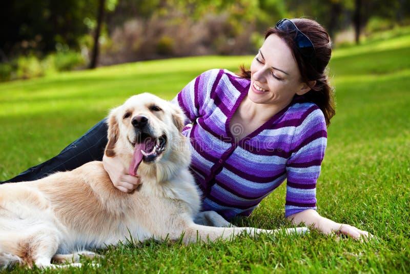 Jeune femme et chien d'arrêt d'or dans l'herbe image stock