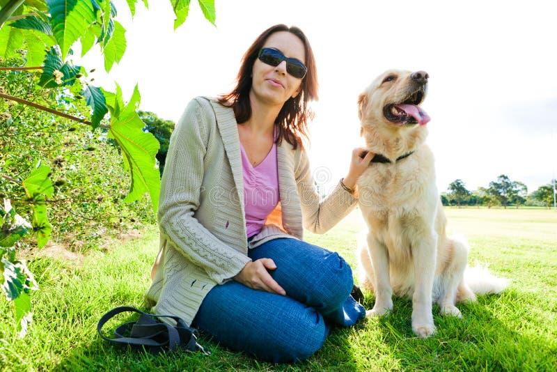 Jeune femme et chien d'arrêt d'or se reposant dans l'herbe  images stock