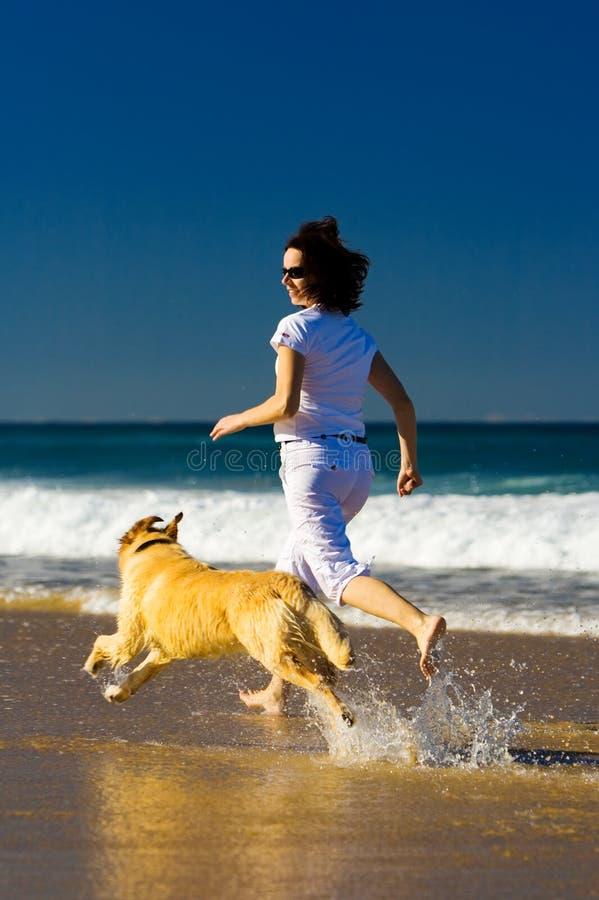 Jeune femme et crabot fonctionnant sur la plage photo libre de droits
