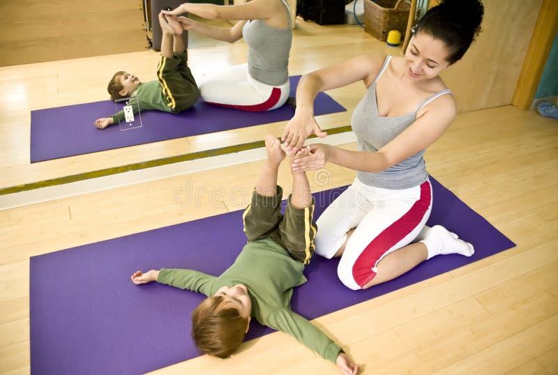 Jeune femme et enfant faisant Pilates photographie stock