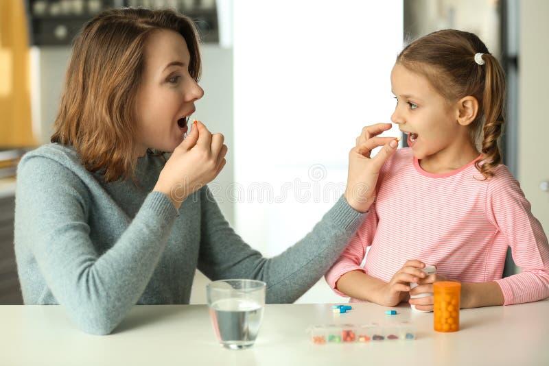Jeune femme et fille prenant des pilules à la table photo stock