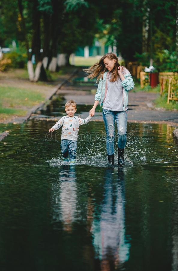 Jeune femme et garçon riant mignon d'enfant en bas âge marchant sur un grand magma en parc d'été après pluie image stock