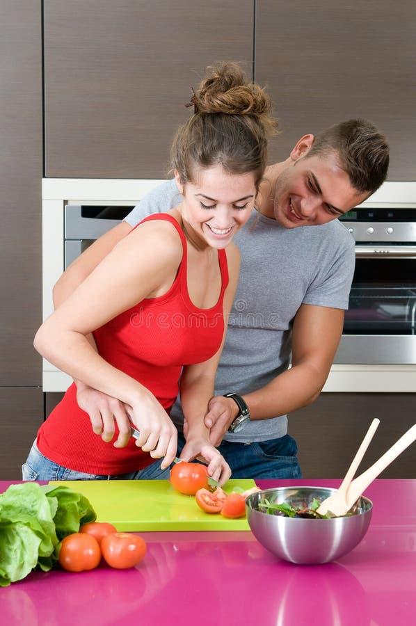 Jeune femme et homme dans la cuisine avec de la salade image libre de droits