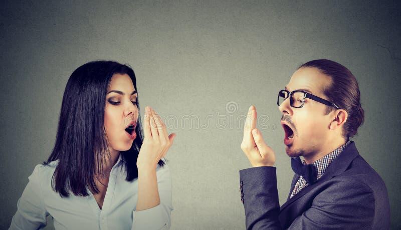 Jeune femme et homme de couples vérifiant leur souffle images stock