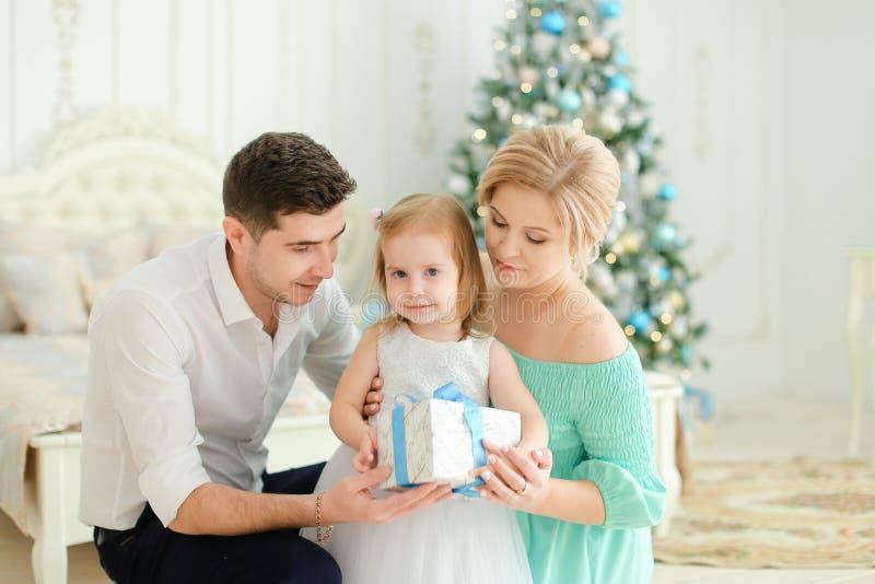 Jeune femme et homme s'asseyant avec la petite fille gardant le présent, arbre de Noël à l'arrière-plan photographie stock libre de droits