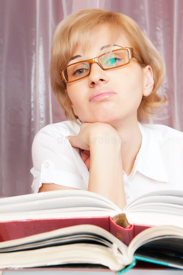 Jeune femme et livre de pile images stock