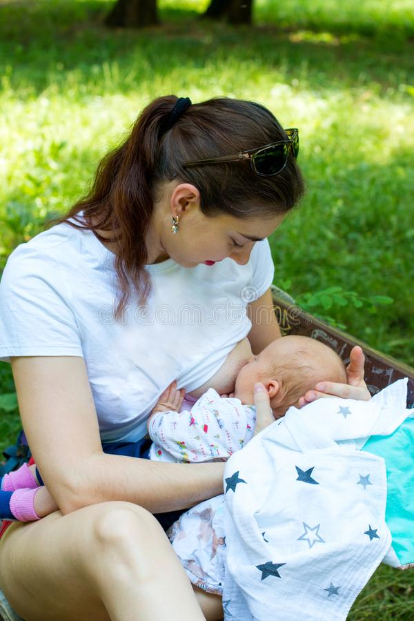 Jeune femme et nouvelle mère allaitant le bébé nouveau-né dehors en parc, jolie maman jugeant infantile dans des mains et soignan images stock