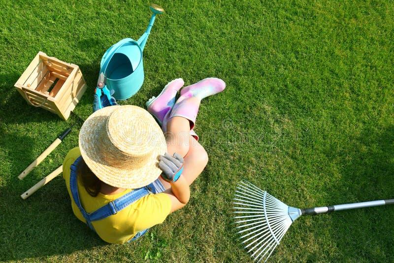 Jeune femme et outils de jardinage sur le vert, au-dessus de la vue photos libres de droits