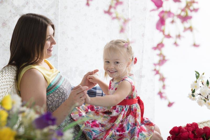 Jeune femme et petite fille sur la terrasse d'été photographie stock libre de droits