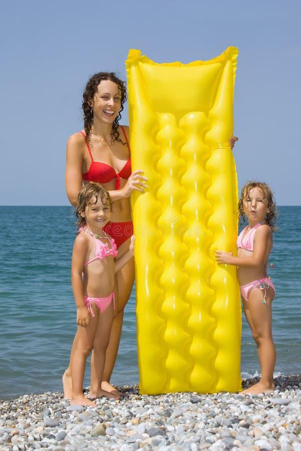 Jeune femme et petites filles restant sur la plage image libre de droits
